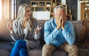 man and woman sitting on couch looking frustrated