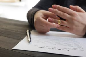 man taking off wedding ring after signing a decree of divorce form