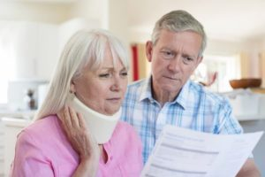 older woman with neck brace holding a document and husband standing near her