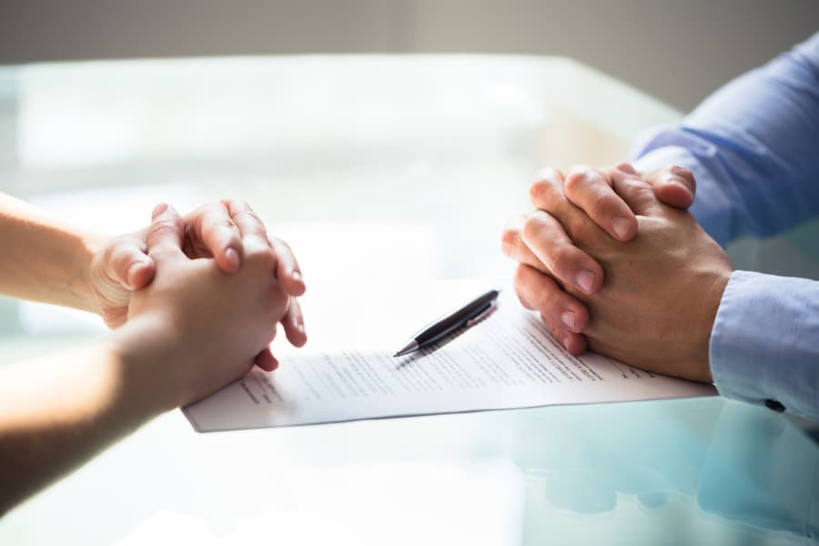 man's and woman's hands folded near a legal document