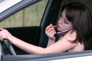 young woman talking on phone, applying lipstick and driving