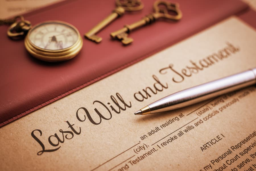pen on top of last will and testament form with a watch and two keys above