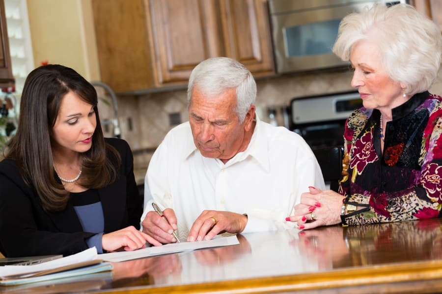 older couple sitting with lawyer signing forms