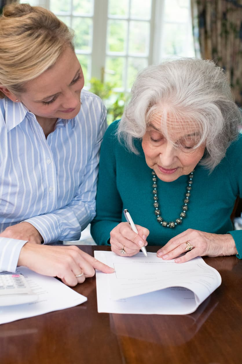 Elderly woman signing form while younger woman sits by her side